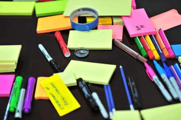Grafiika z notesami, długopisami symbolizujące kreatywność, zarządzanie